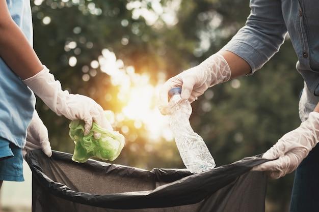 Femme main ramasser les ordures en plastique pour le nettoyage au parc