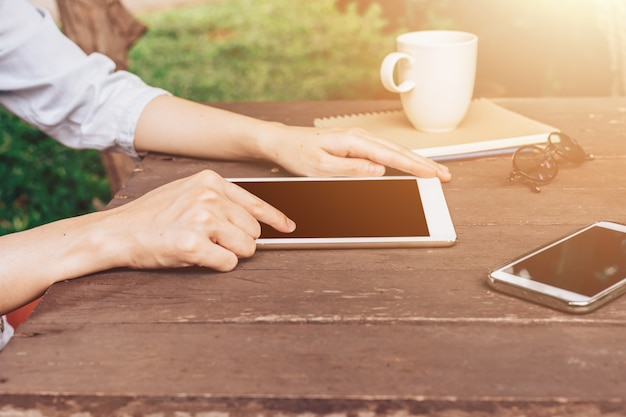 Femme main avec tablette sur table dans le jardin au café avec des tons vintage.
