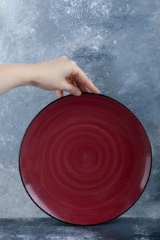 Femme main tenant une assiette vide rouge sur marbre.