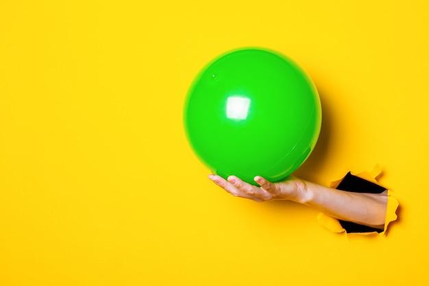 Femme main tenant ballon gonflable vert sur fond jaune vif