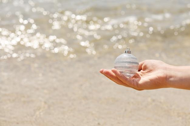 Femme main tenant une boule de noël blanche sur la vague de la mer fond estompée, vacances de noël