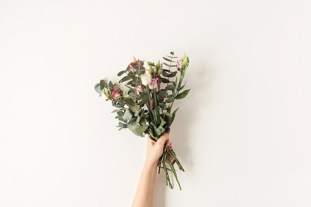 Femme main tenant bouquet de fleurs roses colorées contre le mur blanc