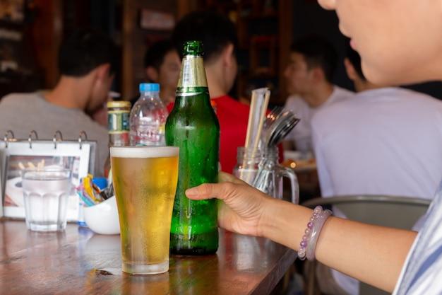 Femme main tenant une bouteille de bière sur la table dans un restaurant.