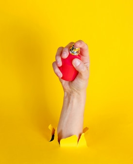 Femme main tenant une bouteille de parfum à travers du papier jaune déchiré. concept de mode minimaliste