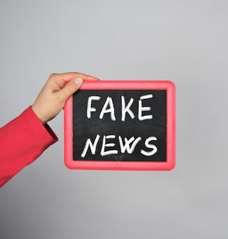 Femme main tenant un cadre rouge avec une inscription de craie fausses nouvelles