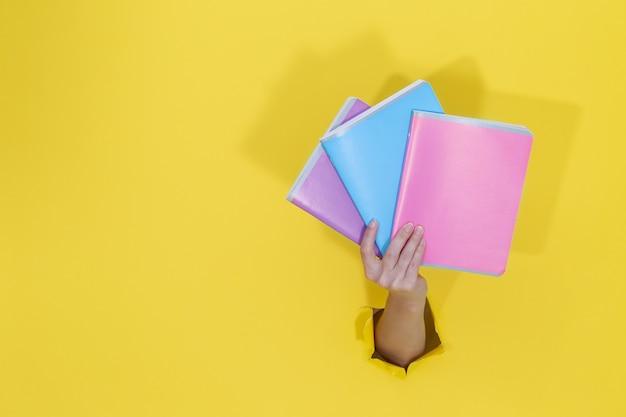 Femme main tenant des cahiers colorés de papier déchiré jaune. retour au concept de l'éducation scolaire. papeterie scolaire et fournitures de bureau. espace pour le texte.