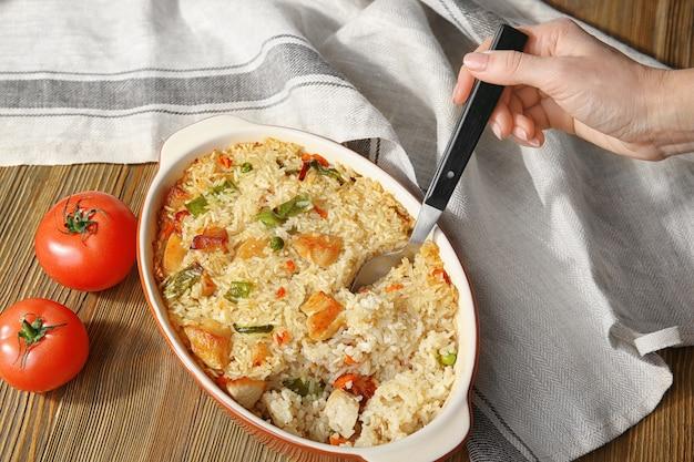 Femme main tenant une cuillère dans un plat allant au four avec du riz et du poulet savoureux