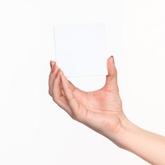 Femme main tenant du papier vierge pour les enregistrements sur fond blanc