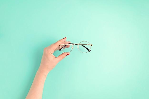 Femme main tenant des lunettes concept d'accessoires de mode