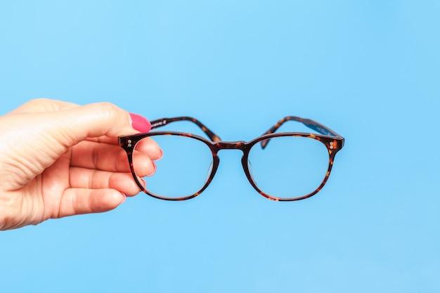 Femme main tenant des lunettes