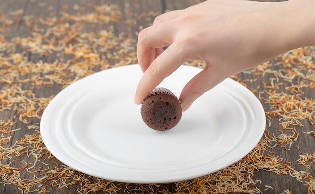 Femme main tenant un muffin au chocolat avec dessus croustillant placé sur une plaque blanche.