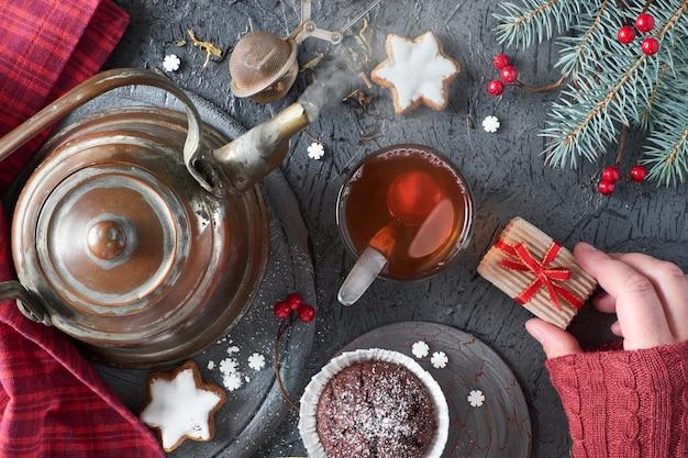Femme main tenant une petite boîte de cadeau sur une table pour le thé