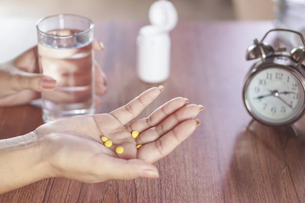 Femme main tenant des pilules avec un verre d'eau en arrière-plan, les soins de santé