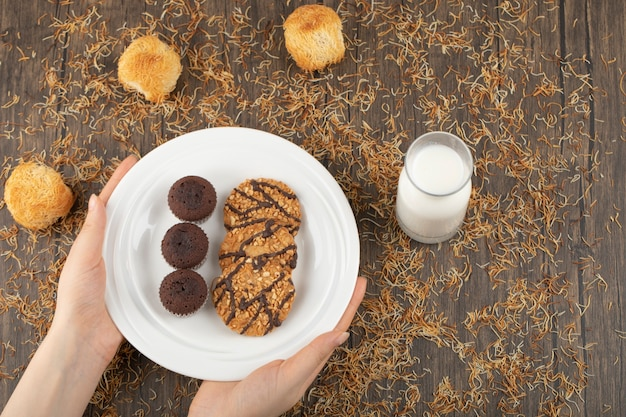 Femme main tenant la plaque de biscuits sucrés sur la surface en bois