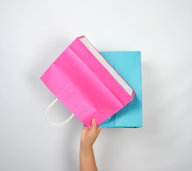 Femme main tenant quatre sacs d'emballage de papier de couleur