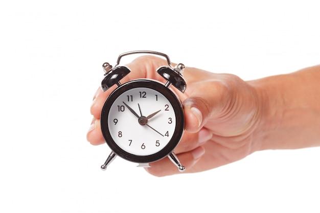 Femme main tenant le réveil