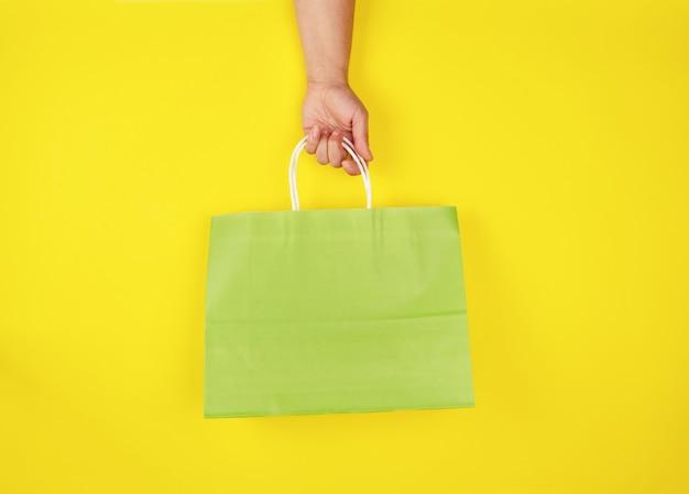 Femme main tenant un sac de papier vert sur jaune