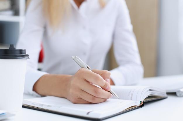 Femme main tenant un stylo argenté prêt à faire