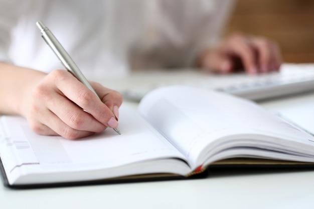 Femme main tenant un stylo argenté prêt à prendre note