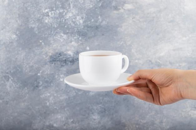 Femme main tenant une tasse blanche de thé noir sur une table en pierre.