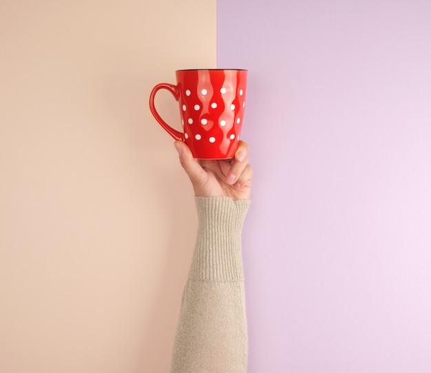 Femme main tenant une tasse en céramique rouge à pois blancs