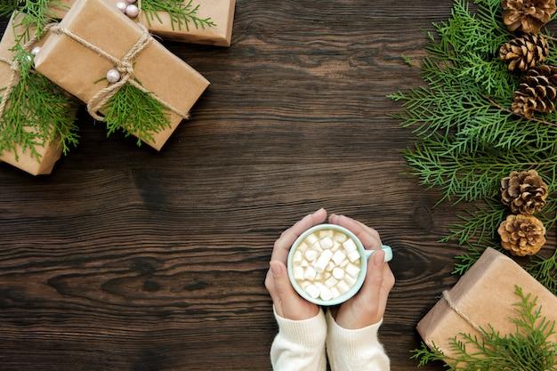Femme main tenant une tasse de chocolat avec des guimauves et des coffrets cadeaux en bois foncé, vue de dessus