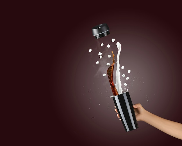 Femme main tenant une tasse thermique en métal noir sur fond marron foncé avec des éclaboussures de café et de lait chauds