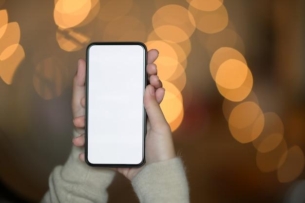 Femme main tenant un téléphone mobile à écran blanc dans la nuit de la rue