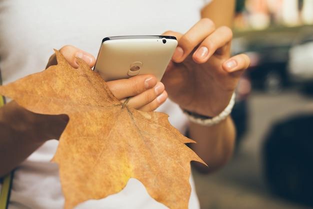 Femme main tenant un téléphone portable et gros plan des feuilles tombées