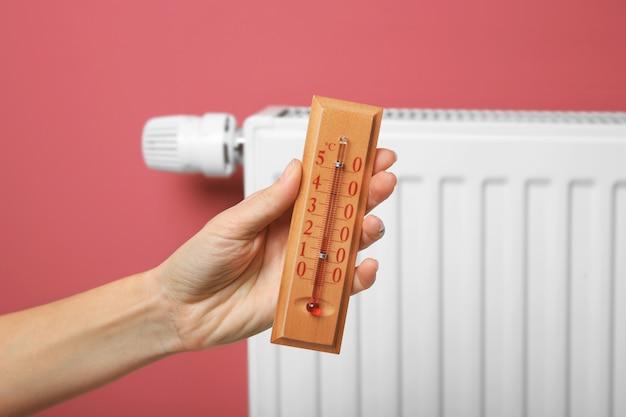 Femme main tenant un thermomètre près de la batterie de chauffage