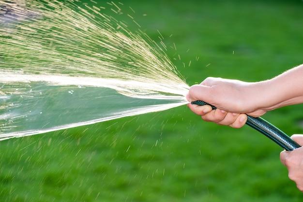 Femme main tenant le tuyau d'eau en caoutchouc faisant de l'eau pulvérisée avec la lumière du soleil