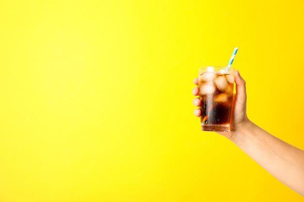 Femme main tenant un verre de cola de glace et tubule