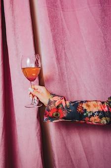Femme main tenant un verre de vin. rideau rose en arrière-plan.