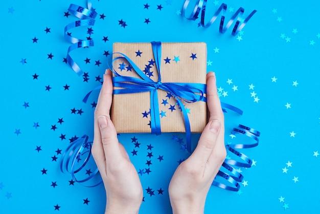 Femme main tenir une boîte cadeau emballée dans du papier kraft