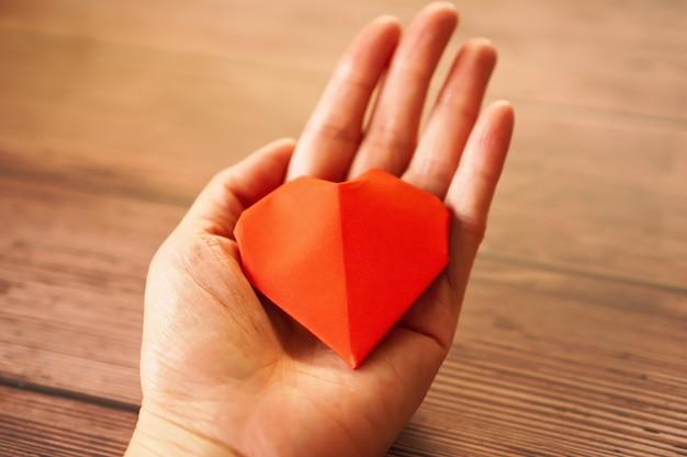 Femme main tenir coeur papier rouge, amour et concept de charité