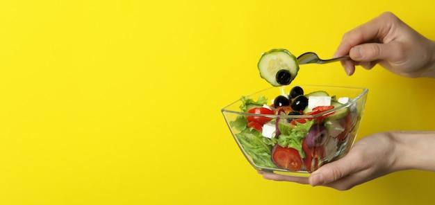Femme main tenir la fourchette et bol de salade grecque sur surface jaune