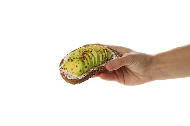 Femme main tenir le pain grillé à l'avocat, isolé sur blanc