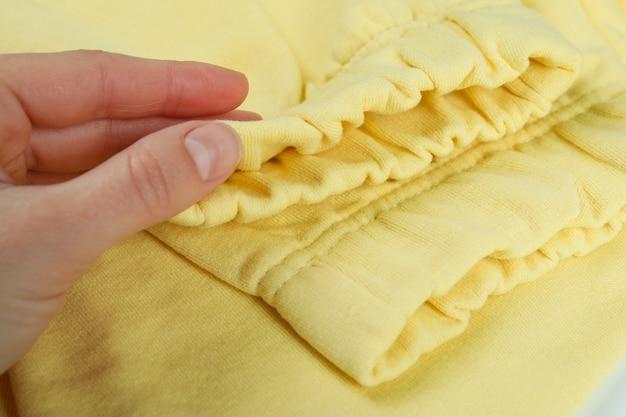 Femme main tenir un pantalon de survêtement jaune, gros plan