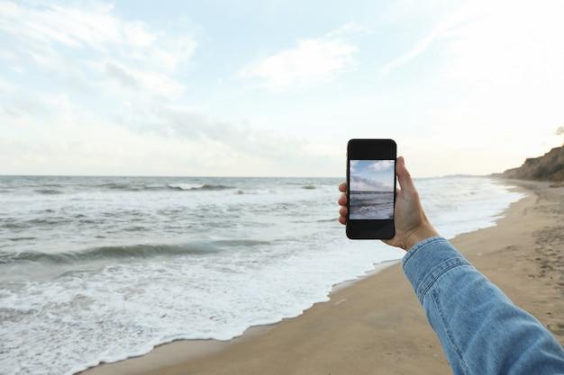 Femme main tenir le téléphone avec selfie sur mer