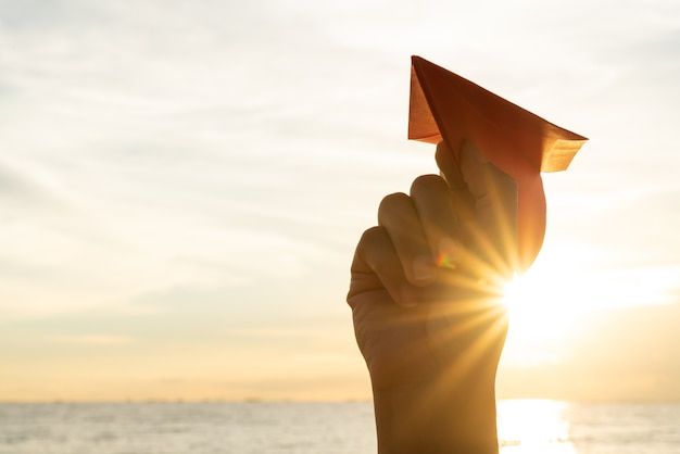 Femme, main, tenue, papier rouge, fusée, pendant, coucher soleil concept de liberté.