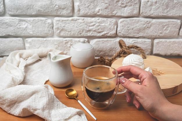 Femme main tient une tasse de verre avec du café sur une table en bois