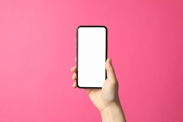 Femme main tient le téléphone sur la surface rose