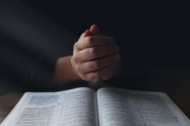 Femme les mains sur la bible. elle lit et prie sur la bible dans un espace sombre au-dessus d'une table en bois.