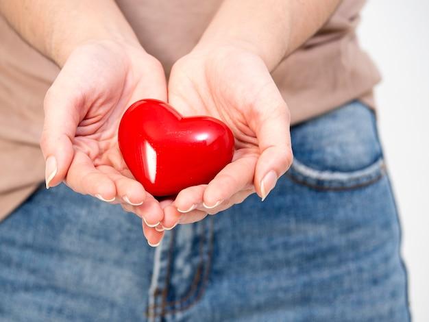 Femme, mains, coeur rouge