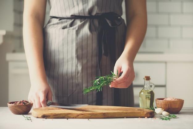 Femme mains coupe romarin vert frais sur planche à découper en bois dans la cuisine blanche