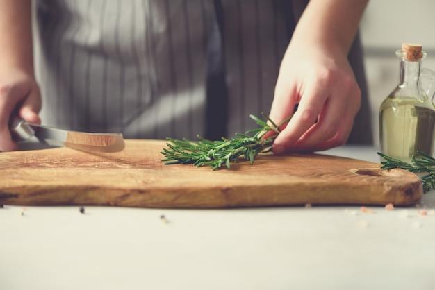 Femme mains coupe romarin vert frais sur planche à découper en bois dans la cuisine, intérieur. espace de copie. cuisine faite maison, recette saine. emmenez-moi au travail