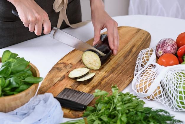 Femme mains couper l'aubergine avec un couteau sur planche de bois le processus de cuisson