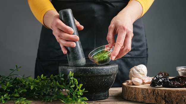 Femme mains cuisson verser le persil dans le mortier