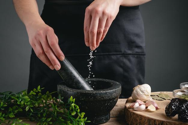 Femme mains cuisson verser le sel dans le mortier