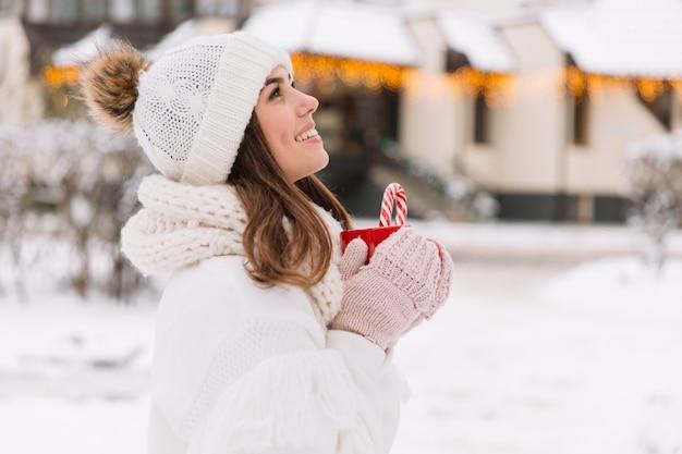 Femme mains dans les gants tenant une tasse confortable avec du cacao chaud, du thé ou du café et une canne en bonbon.